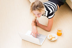 Girl looks in the laptop from the couch.  Stock Photos