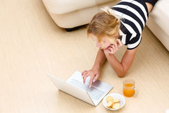 Girl looks in the laptop from the couch.  Royalty Free Stock Photo