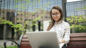 The girl looks at the laptop screen and typing on the keyboard. Elegant young woman sitting with a laptop outdoors. Remote work. The girl looks at the laptop stock video footage
