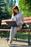 The girl looks in a laptop. Young girl in a white suit with a notebook carefully reads Stock Image