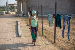 The girl looks at the laundry. A beautiful girl looks with astonishment at the washed clothes hanging on a barbed wire fence Royalty Free Stock Image