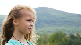 The girl looks long into the distance and brings binoculars to her eyes. Hair fluttering in the wind.  stock video