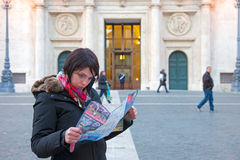 Girl looks at the map of Rome. Rome, Italy - February 28, 2013: Girl looks at the map of Rome in Piazza di Montecitorio seat of the Chamber of Deputies of the Stock Image
