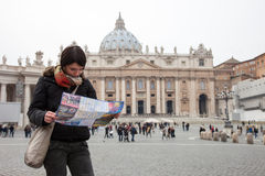 Girl looks at the map of Rome in piazza San Pietro. Rome, Italy - March 1, 2013: St. Peter's Square is the square in front of the basilica of St. Peter. Located Stock Photo