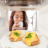 Girl looks in a microwave Royalty Free Stock Images
