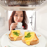 Girl looks in a microwave Stock Photo