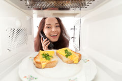Girl looks in a microwave Stock Photos