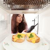 Girl looks in a microwave Stock Images