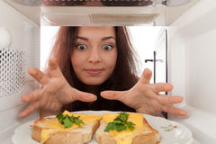 Girl looks in a microwave Stock Photography