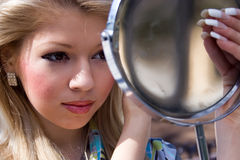 Girl looks in the mirror Royalty Free Stock Images
