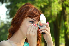 The girl looks in the mirror. Red-haired girl looking in the mirror Royalty Free Stock Photo
