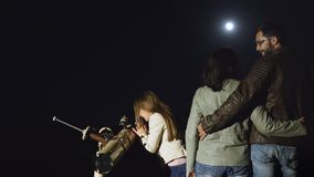 Happy family watching the moon in a telescope at night. A girl looks at the moon through a telescope with her parents at night stock footage