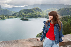 The girl looks at the mountain views. valley view and lake on Alps the background. Travel Slovenia, Europe. Bled Lake with Island, Castle and Alps Mountain on Stock Photography
