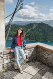 The girl looks at the mountain views. valley view and lake on Alps the background. Travel Slovenia, Europe. Bled Lake with Island, Castle and Alps Mountain on Stock Photo