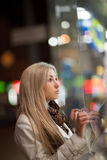 Girl looks at night shopwindow Royalty Free Stock Photography