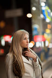 Girl looks at night shopwindow Royalty Free Stock Photos