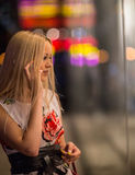 Girl looks at night shopwindow Stock Photos