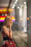 Girl looks at night shopwindow Stock Photography