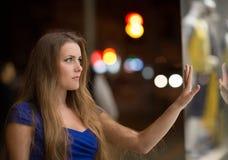 Girl looks at night shopwindow Stock Photos
