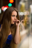 Girl looks at night shopwindow Royalty Free Stock Images