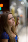Girl looks at night shopwindow Royalty Free Stock Image