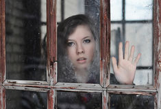 The girl looks at old window. Young girl looking at the camera through the glass of the old windows Stock Photo
