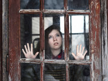 The girl looks at old window. Young girl looking at the camera through the glass of the old windows Royalty Free Stock Image