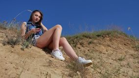 Girl looks online in a smartphone on the nature. Girl playing online games Royalty Free Stock Photos