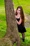 The girl looks out from behind a tree Royalty Free Stock Photo