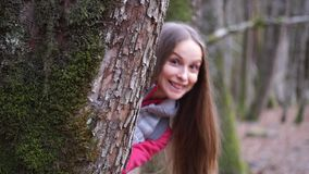 Girl looks out from behind a tree. stock video