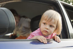 The girl looks out of the car Stock Image