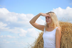 Girl looks out from hay Stock Image