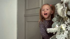 The girl looks out for a New Year tree. The lovely fair-haired girl plays near a Christmas tree. Slow mothion. The girl looks out for a New Year tree. The lovely stock video footage