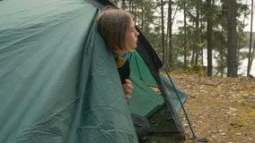 Girl looks out of the tent in the forest.  stock video