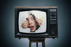 A girl looks out from the TV. Stock Image