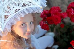 Girl looks out from under the lace parasol Stock Photos