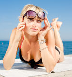 The girl looks out from under sunglasses. Attractive young blond woman in sunglasses at the sea Stock Photo