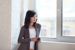 Girl looks out of the window Royalty Free Stock Photo
