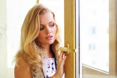 Girl looks out the window Royalty Free Stock Photography