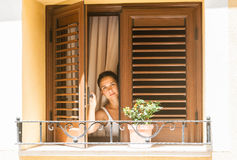 Girl looks out of the window Royalty Free Stock Image
