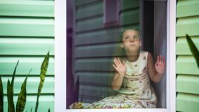 A girl looks out the window at the rain, afraid. Young Girl sits on the windowsill and looks out the window at the rain, afraid, sparkles with lightning stock video
