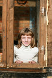 Girl looks out from a wooden window frame Stock Photo