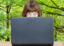 Girl looks over cover of laptop and green forest Stock Images