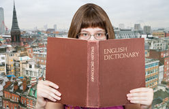 Girl looks over English Dictionary and skyline Stock Image