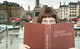 Girl looks over English Dictionary and square Stock Photos