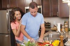 Girl looks over mans shoulder as he prepares dinner. Man prepares vegetables while his girlfriend looks over his shoulder royalty free stock photography