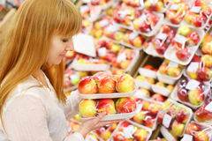 Girl looks at packed apples in store Stock Image