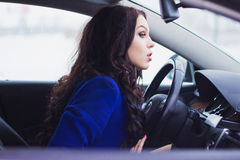 Girl looks pensively into the windshield of the car Royalty Free Stock Photos