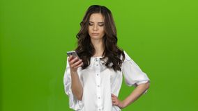 Girl looks into the phone, selects the information she needs. Green screen. Girl looks at the phone, chooses the information she needs, she`s having fun, she`s stock footage