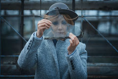 Girl looks through a piece of glass Royalty Free Stock Photo